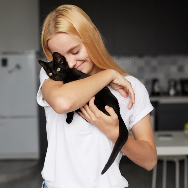 Close up of young blonde girl at the kitchen holds on hands, caresses, stroking, hugs black little cat, cute tenderly smiling, eyes closed, dressed in a domestic white T-shirt, kitchen background